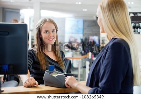 Portrait of young female sales clerk standing by counter with customer at parlor - stock photo