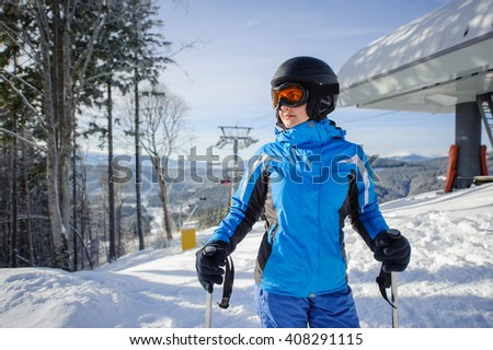 Portrait of young female skier on the top of ski slope with ski-lift and mountains on the background. Winter sports concept. Carpathian Mountains, Bukovel, Ukraine - stock photo