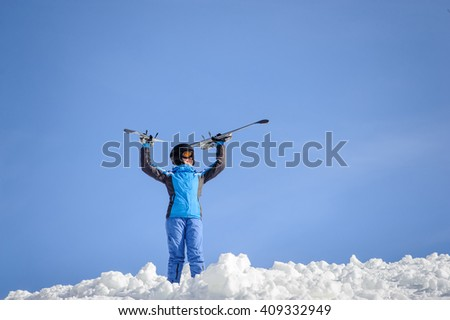 Portrait of young female skier standing on top of the mountain against blue sky on a sunny day. Woman is holding skis up smiling and looking into the distance. Winter sports concept. - stock photo