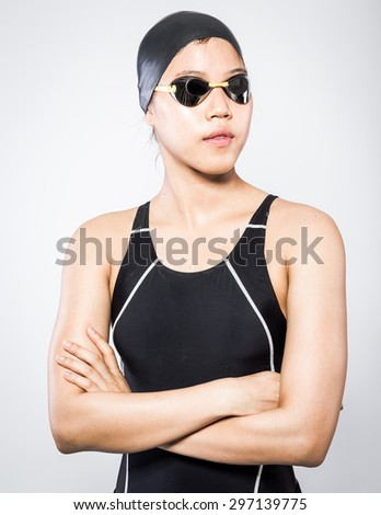 portrait of young female swimmer in blue swimsuit with goggle and swimming hat in studio set - stock photo