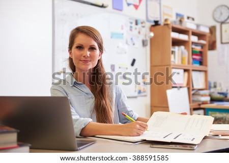 Portrait of young female teacher at desk looking to camera - stock photo