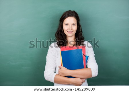 Portrait of young female teacher holding files against chalkboard in class - stock photo
