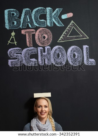Portrait of young female teacher looking at camera by the blackboard