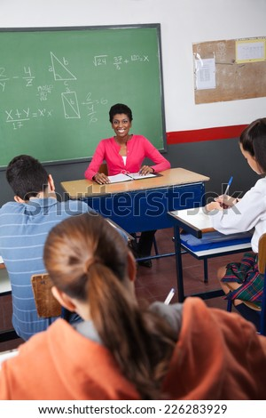 Portrait of young female teacher sitting with students in classroom - stock photo