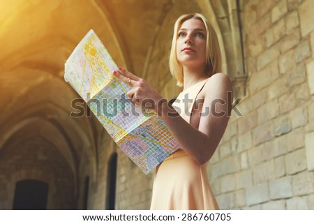 Portrait of young female tourist checking out the sights while reading a map, gorgeous woman holding a map while touring abroad,stylish hipster studying a map while standing in antique town in summer - stock photo