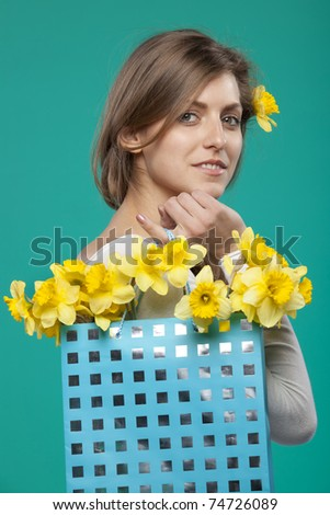 Portrait of young female with bunch of flowers in the paper-bag isolated on turquoise background - stock photo