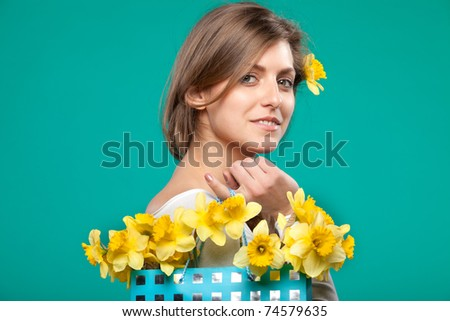 Portrait of young female with bunch of flowers in the paper-bag over her shoulder isolated on turquoise background - stock photo