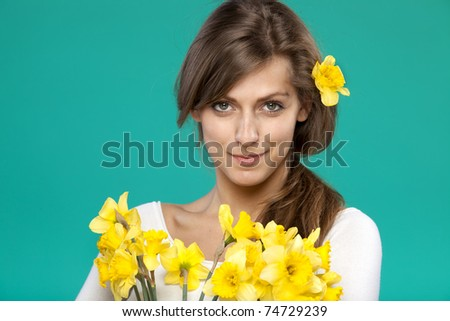 Portrait of young female with bunch of flowers isolated on turquoise background - stock photo
