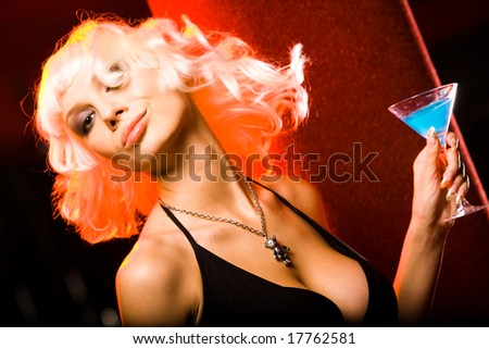 Portrait of young female with cocktail having fun in a night club