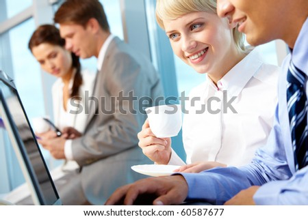 Portrait of young female with cup of coffee looking at laptop monitor in office and interacting with partner - stock photo