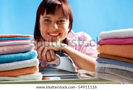 Portrait of young female with iron between two stacks of colorful towels smiling at camera