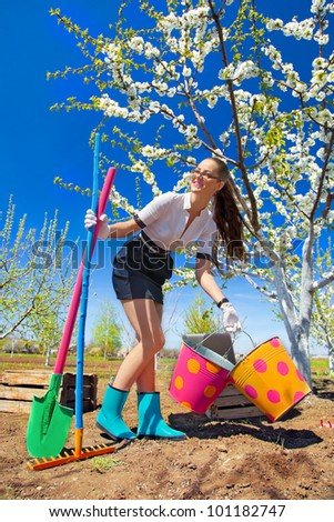Portrait of young female with rakes and spade on garden