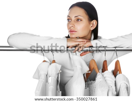 Portrait of young female with selection of winter clothes. Space for text. Sale season concept.  - stock photo