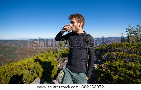 Portrait of young fit male hiker drinking tea on top of the mountain on a warm sunny day, fall time. Beautiful overview point. Lifestyle and sport concept. - stock photo