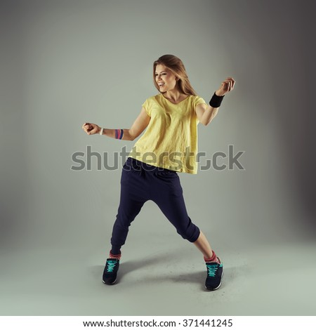 Portrait of young fitness female dancing zumba in studio. Energetic woman doing aerobics exercise. Sport, leisure activity and lifestyle.  - stock photo