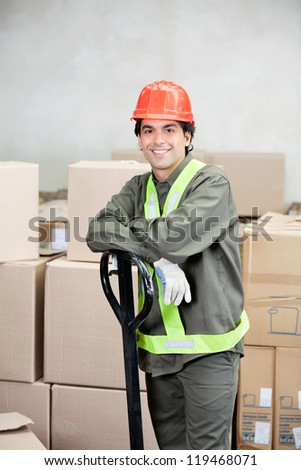 Portrait of young foreman standing at warehouse - stock photo