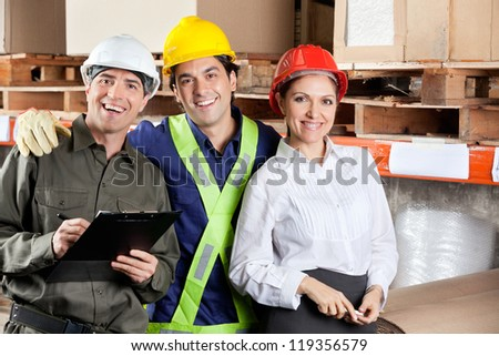 Portrait of young foreman with supervisors smiling together at warehouse - stock photo
