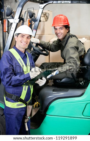 Portrait of young forklift driver and supervisor at warehouse - stock photo