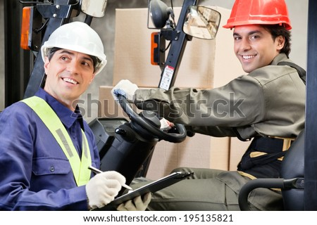 Portrait of young forklift driver with supervisor writing notes at warehouse - stock photo