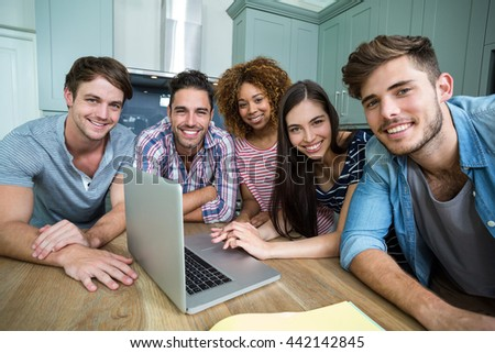 Portrait of young friends smiling while using laptop on table at home - stock photo