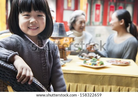Portrait of young girl at family meal - stock photo