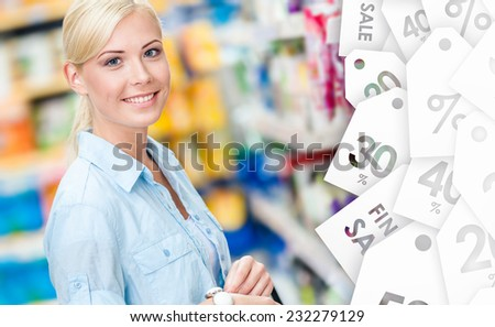 Portrait of young girl at the shop standing near the shelves with cosmetics. Sale time - stock photo