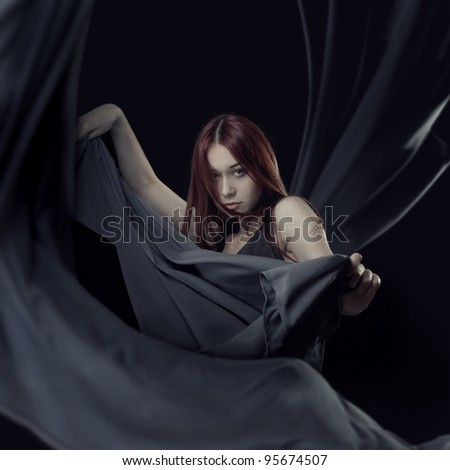 portrait of young girl dancing with long grey cloth in hands