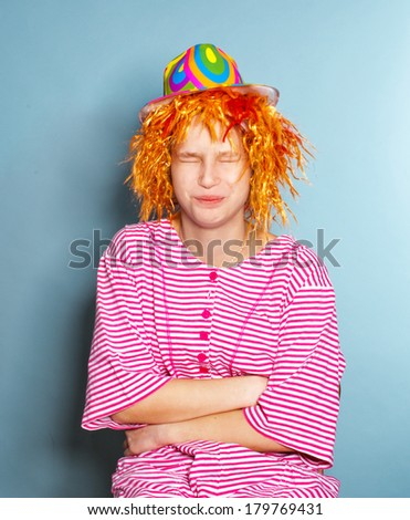 portrait of  young girl dressed in funny striped suit, a red wig and a colorful hat - stock photo