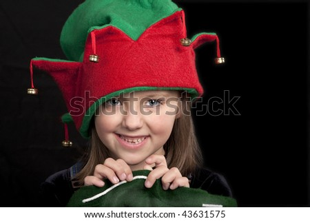 Portrait of young girl dressed in red and green Christmas hat. - stock photo