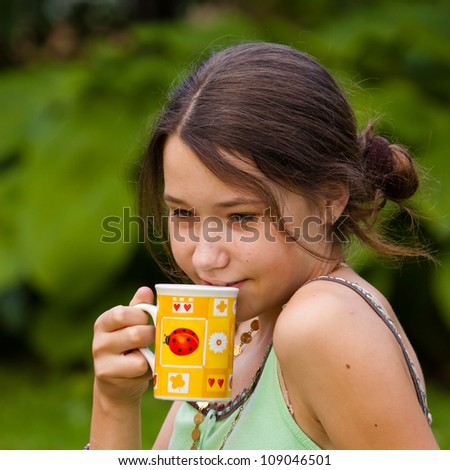 Portrait of young girl drinking tea outdoors - stock photo