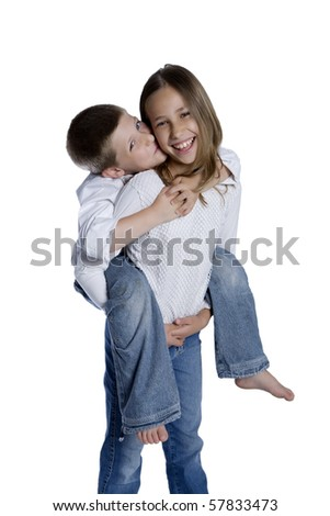 Portrait of young girl giving boy piggyback ride, studio shot isolated on white - stock photo