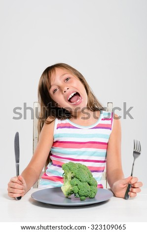 Portrait of young girl happy at meal time to eat her fresh vegetables, healthy eating concept - stock photo