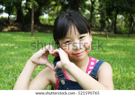 Portrait of young girl having a good time in the park, hands making heart symbol.