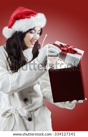 Portrait of young girl in christmas hat wearing warm clothes, opens a christmas gift with miracle light - stock photo
