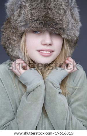 Portrait of young girl in fur hat - stock photo