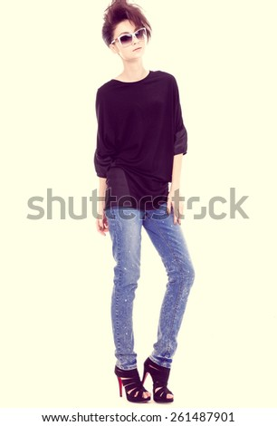 Portrait of young girl in jean wearing sunglasses posing - stock photo