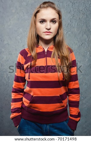 Portrait of young girl in striped sweatshirt and blue jeans - stock photo