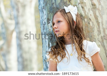 Portrait of young girl in white dress standing next to tree. - stock photo