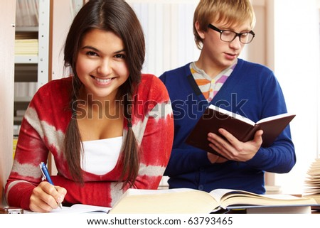 Portrait of young girl looking at camera on background of reading guy in college library - stock photo
