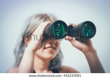 portrait of young girl looking through a binoculars - stock photo