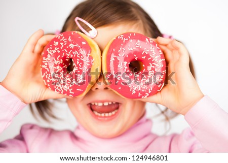 Portrait of young girl looking through two pink donuts, white background - stock photo