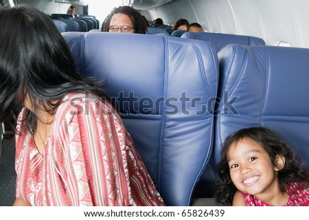 Portrait of young girl on airplane - stock photo