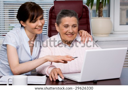 Portrait of young girl pointing at laptop monitor while embracing her grandmother - stock photo
