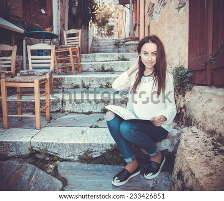 Portrait of young girl reading book on steps with cat - stock photo