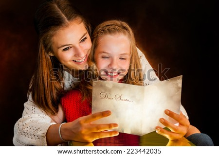 Portrait of young Girl reading Christmas card to younger sister. - stock photo