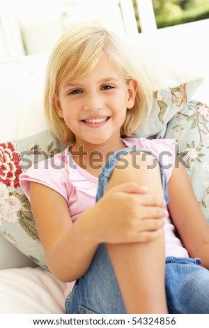 Portrait Of Young Girl Relaxing On Sofa - stock photo