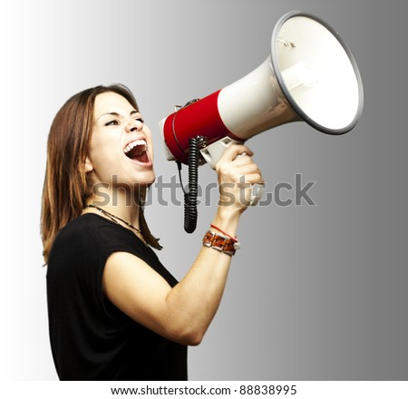 portrait of young girl shouting with megaphone over grey background