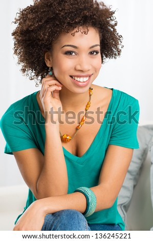 Portrait Of Young Girl Sitting On Couch - stock photo