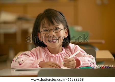Portrait of young girl smiling in classroom - stock photo