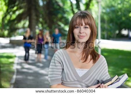 Portrait of young girl smiling while her classmates walking in the background - stock photo